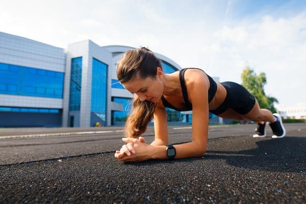 Coureur d'athlète en cours d'exécution sur une piste d'athlétisme entraînant son cardio. femme jogging pour course de compétition au stade extérieur d'été.