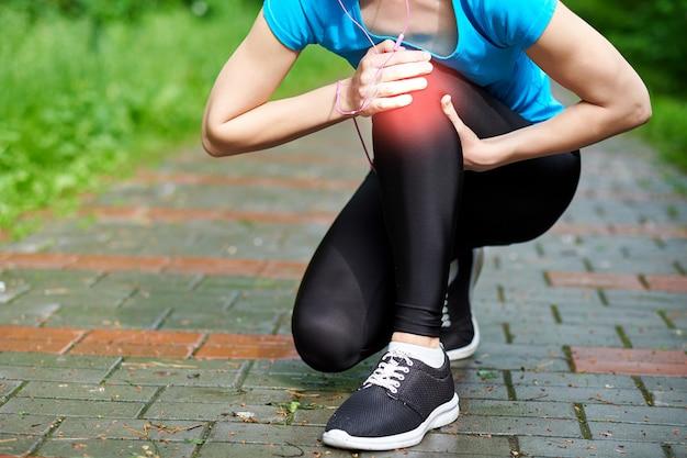 Coureur d'athlète féminine touchant le genou dans la douleur, fitness femme qui court dans le parc d'été. mode de vie sain et concept de sport