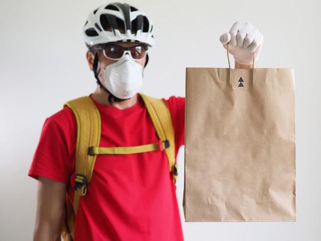 Le coureur cycliste porte un masque facial et des gants livre le sac en papier. service de livraison pendant le coronavirus de quarantaine.