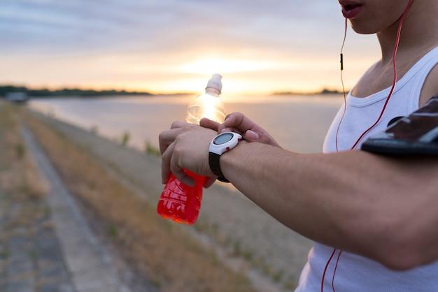 Coureur dans le parc à l'aide d'une montre intelligente