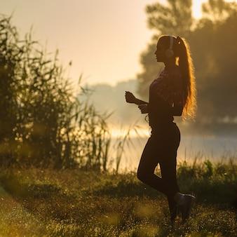 Coureur féminin en cours d'exécution dans la nature au lever du soleil