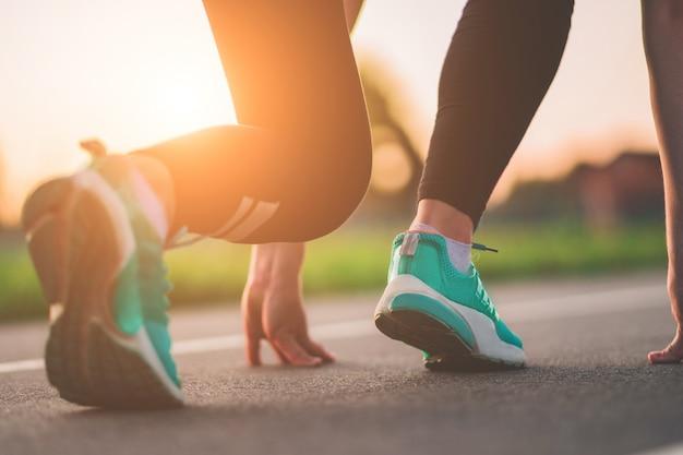 Coureur de femme athlétique sur la ligne de départ pour courir. sports et mode de vie sain