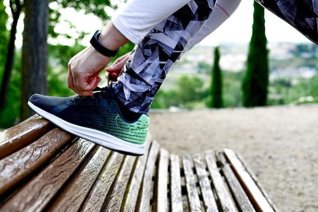 Coureur de femme attachant des chaussures de course avant de courir pour faire de l'exercice le matin. coureur de femme vérifiant la chaussure afin de se préparer à courir. concept en cours d'exécution.