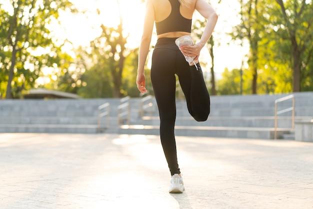Coureur de femme étirant les jambes avant d'exercer le parc d'été matin femme athlétique d'âge moyen réchauffant le corps avant de courir personne de race blanche réchauffer le jogging chemise blanche habillée short piste de course