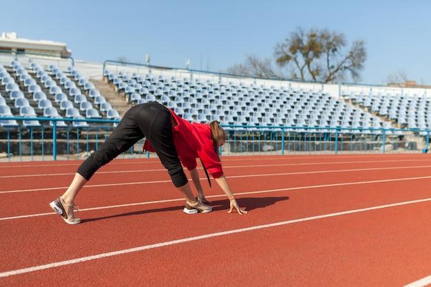 Coureur de femme jeune fitness se réchauffer avant de courir sur piste