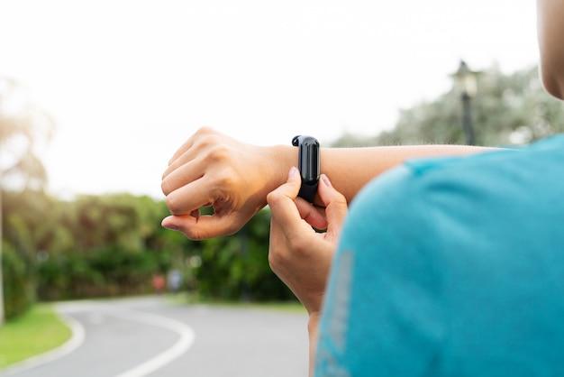 Coureur de femme de remise en forme mise en place montre intelligente avant de courir