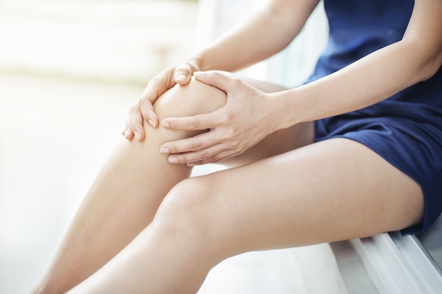 Coureur de femme souffrant de douleur au genou assis sur le sol