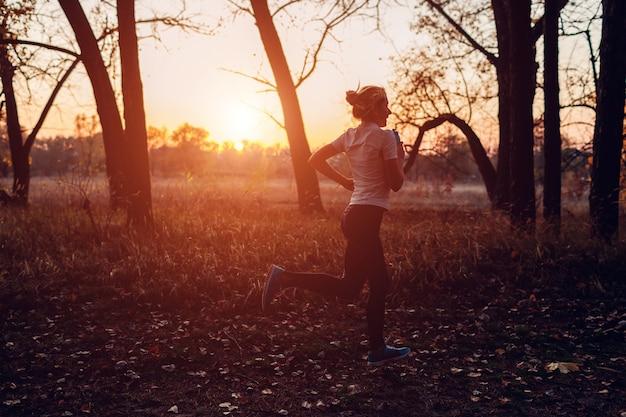 Coureur de formation en automne parc. femme qui court avec une bouteille d'eau au coucher du soleil. mode de vie actif. silhouette