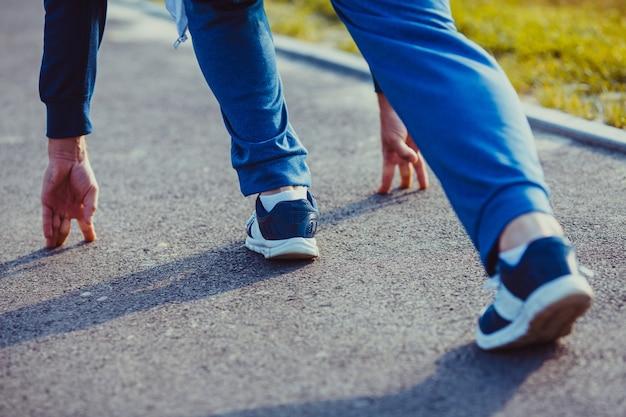 Un coureur d'homme en vêtements de sport à une position avant de courir