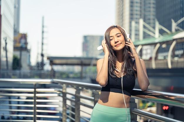 Coureur de jeune femme asiatique au repos et écouter de la musique