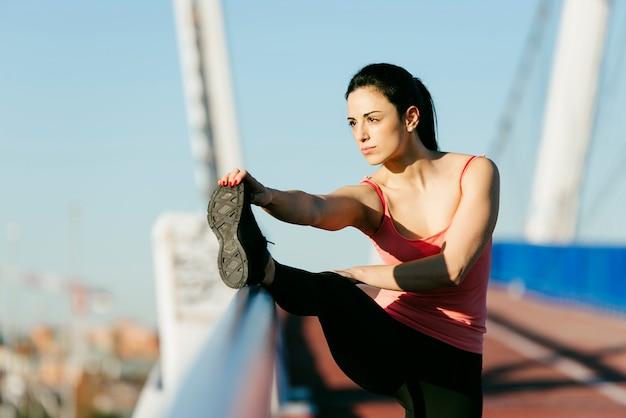 Coureur de jeune fitnesswoman étirement des jambes après run.sport concept.