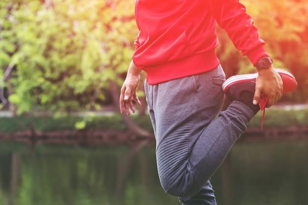 Coureur de jeune homme s'étirant pour se réchauffer avant de courir ou de s'entraîner sur la route du parc. exercice d'athlétisme d'athlétisme. concept de remise en forme et de mode de vie sain.