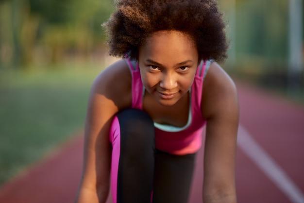 Coureur de jolie fille debout en position de départ avant le sprint