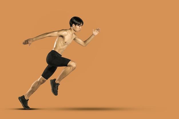 Coureur masculin jogging isolé. sur fond orange.