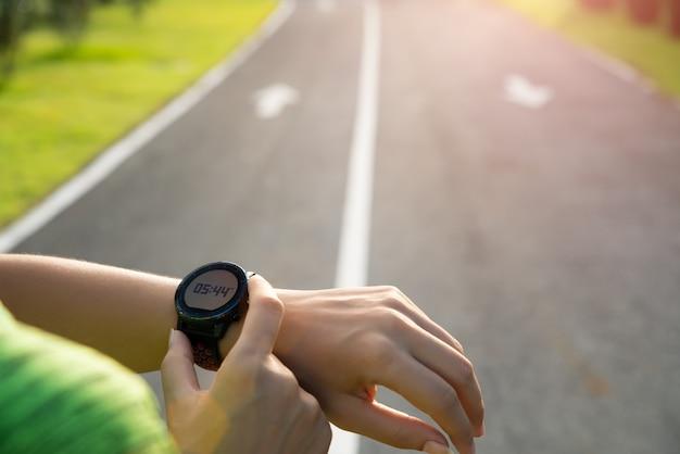 Coureur mettant en place une montre intelligente avant l'entraînement pendant le coucher du soleil. exercice.