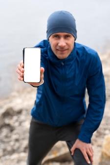 Coureur montrant un téléphone vide dans la nature