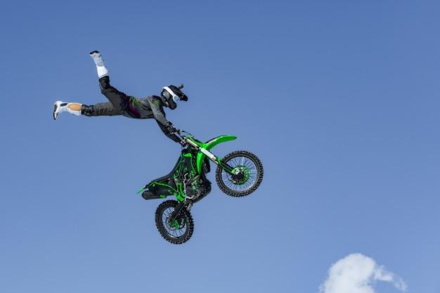 Coureur sur une moto en vol, saute et décolle sur un tremplin contre le ciel bleu