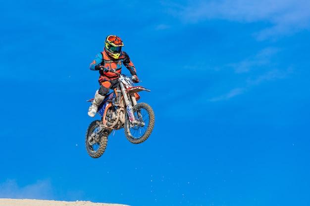 Coureur sur une moto en vol, saute et décolle sur un tremplin contre le ciel.