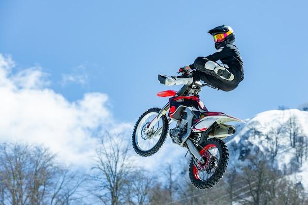 Coureur sur une moto en vol, saute et décolle sur un tremplin contre les montagnes enneigées