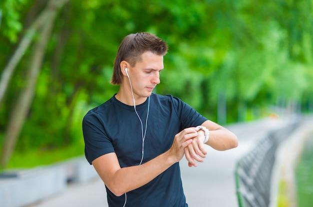 Coureur regardant le moniteur de fréquence cardiaque de la montre intelligente ayant la pause pendant la course