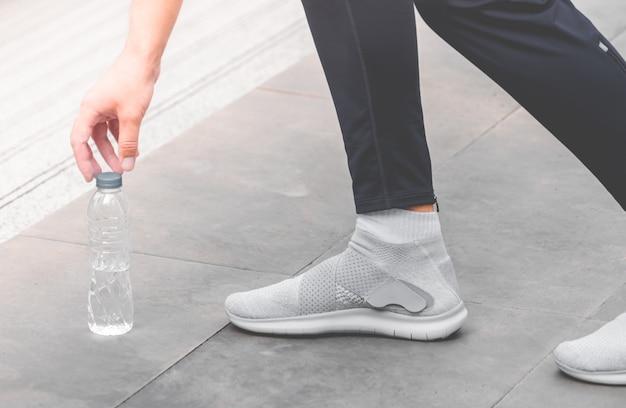 Coureur sportif prend de l'eau potable du sol