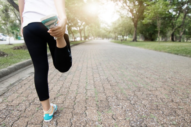 Coureur sportif ver et exercer avant de courir, entraînement femme dans le parc