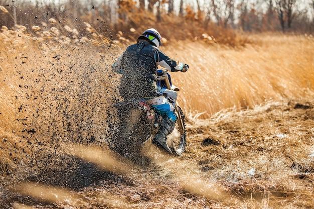 Coureur de vélo d'enduro sur un champ avec de l'herbe sèche en automne. la moto dérape et fait beaucoup d'éclaboussures de boue. focus sur la boue