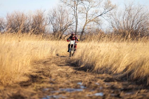Coureur de vélo d'enduro sur un champ avec de l'herbe sèche en automne