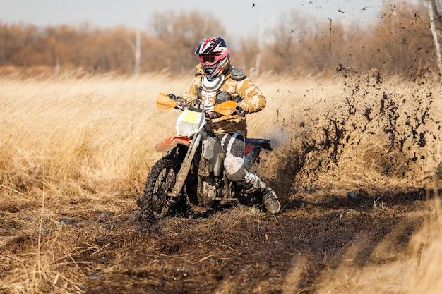Coureur de vélo d'enduro dans un champ avec de l'herbe sèche en automne. la moto dérape et fait beaucoup d'éclaboussures de boue