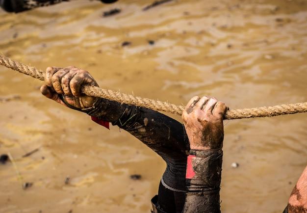 Coureurs de course de boue, en surmontant des obstacles en utilisant des cordes. détails des mains.