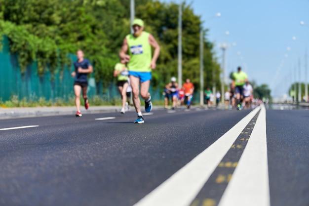 Coureurs sur route de la ville. marathon en cours d'exécution, copiez l'espace. compétition extérieure de sprint de rue