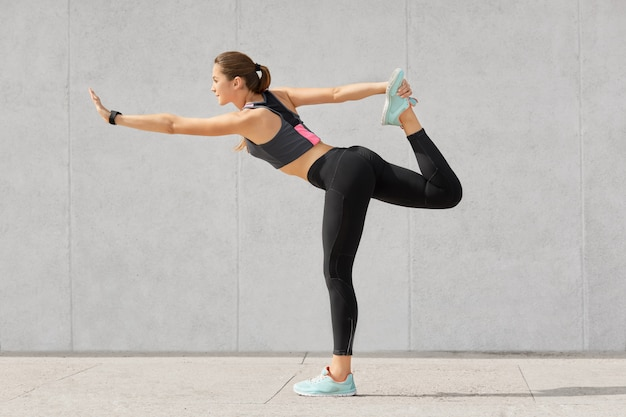 La coureuse a une belle silhouette, étire les jambes avant de courir, se réchauffe, soulève les jambes, pratique le yoga, porte des chaussures de sport