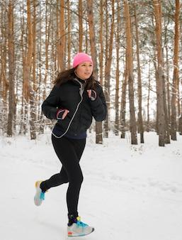 Coureuse de jogging dans la forêt d'hiver froid portant des vêtements de course sportifs chauds et des gants d'écouteurs.