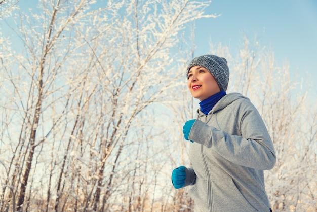 Coureuse de jogging dans la forêt d'hiver froid portant des vêtements et des gants de course sportifs chauds