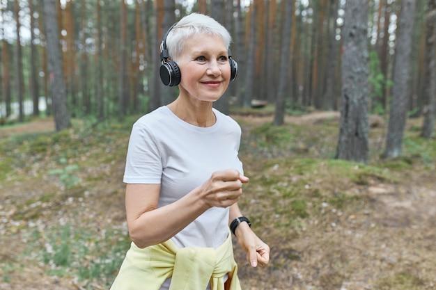 Coureuse mature active portant des vêtements de sport et des écouteurs sans fil, écoutant de la musique avec des écouteurs.