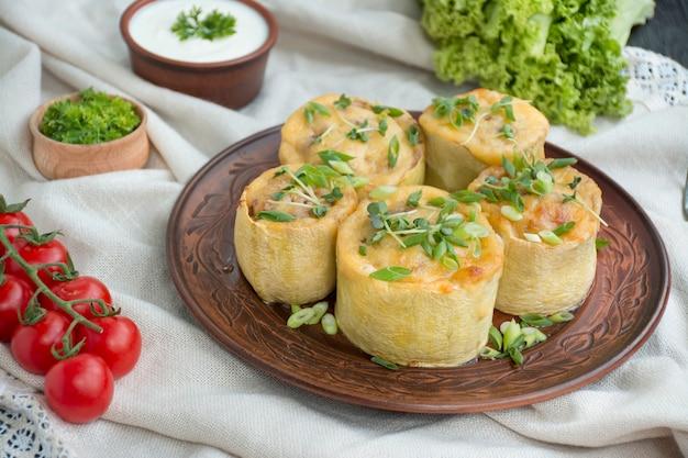 Courge farcie de viande hachée, de légumes et saupoudrée de fromage à pâte dure. vue de côté.