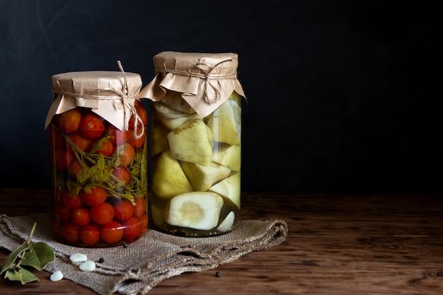 Courge marinée et tomates dans un bocal sur une table en bois