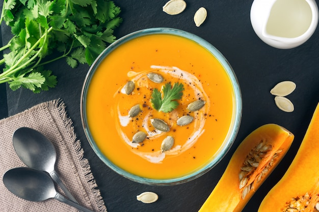 Courge musquée ou soupe à la citrouille dans un bol. ingrédients, crème, coriandre, tranches de citrouille et graines sur ardoise. nourriture végétarienne saine. halloween, dîner de thanksgiving. espace de copie.