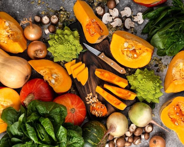 Courge en tranches et citrouille hachée avec différents légumes sur la table.