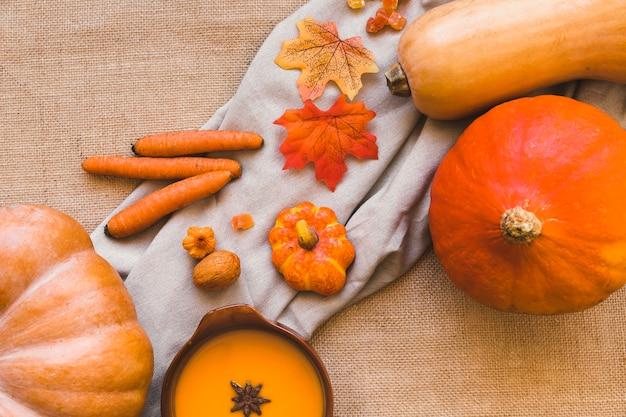 Courges et carottes près des feuilles et de la soupe