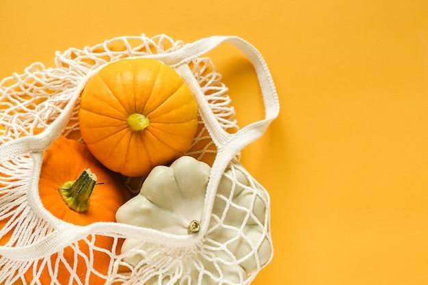 Courges de légumes de récolte fraîches citrouille, courge pattypan dans sac de maille écologique sur fond jaune.