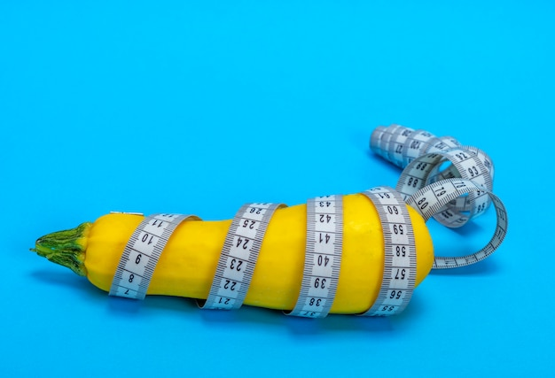 Courgette crue jaune enveloppée dans un ruban à mesurer
