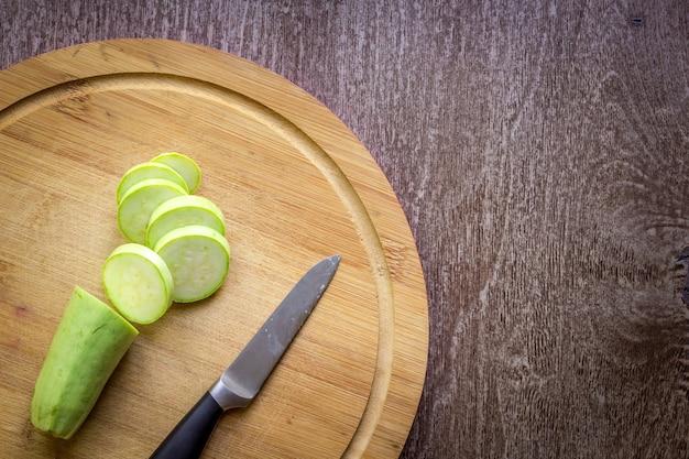 Une courgette tranchée sur une planche de bois fond de bois