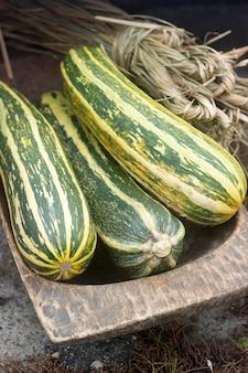 Courgettes ou courgettes et un paquet de paille dans une auge en bois lors d'une foire agricole.
