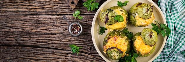 Courgettes farcies de viande hachée, de fromage et d'herbes vertes. cuit au four. bannière.