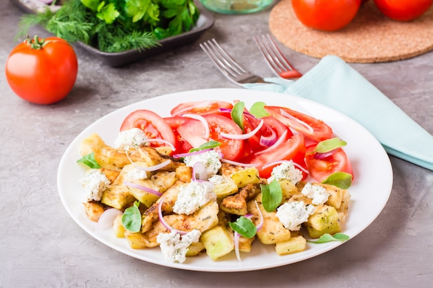Courgettes frites avec du fromage feta, des tomates, des herbes et des oignons sur une assiette