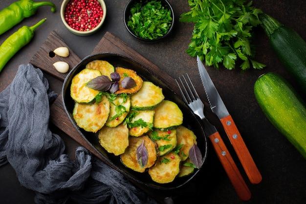Courgettes frites avec piment rouge, basilic et persil dans une poêle en fonte sur une vieille surface sombre