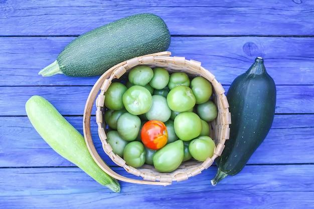 Courgettes et tomates pas mûres. légumes biologiques crus frais sur des planches de bois à l'extérieur.