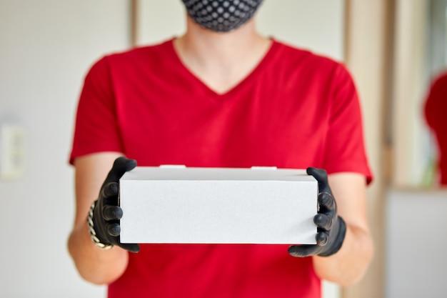 Courier, livreur dans des gants en latex médical livre en toute sécurité les achats en ligne pendant l'épidémie de coronavirus.