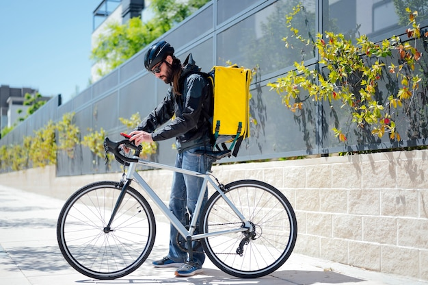 Courier à vélo livrant de la nourriture en ville à l'aide de smartphone